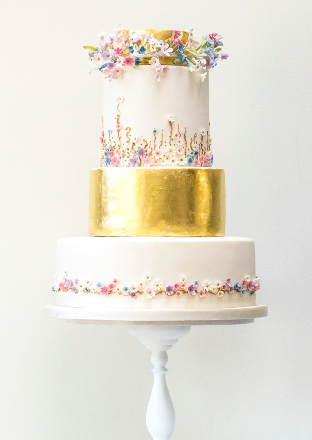 "Golden Meadows is very much a Queen's cake, with brilliant shimmering second tier, and the tiny flowers in a circle. Rosalind said ""This cake was inspired by tiny meadow flowers and floral hair garlands, which when combined with the gold leaf create a magical and ethereal feel."""